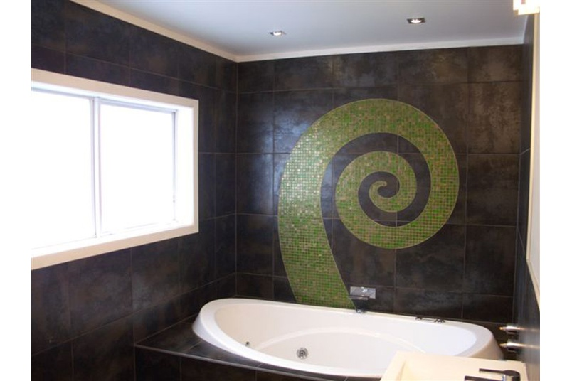 Bathroom wall inlayed with a koru design using Bisazza's Gemme mosaics